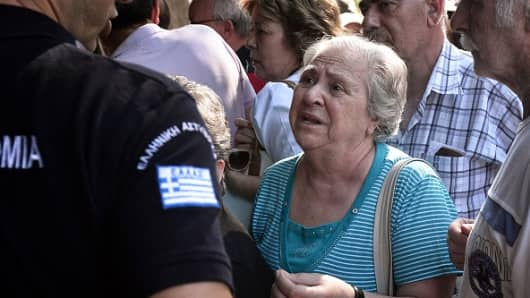 A woman talks to a police officer as she waits outside a national Bank branch, as banks only opened for pensioners to allow them to get their pensions, with a limit of 120 euros.